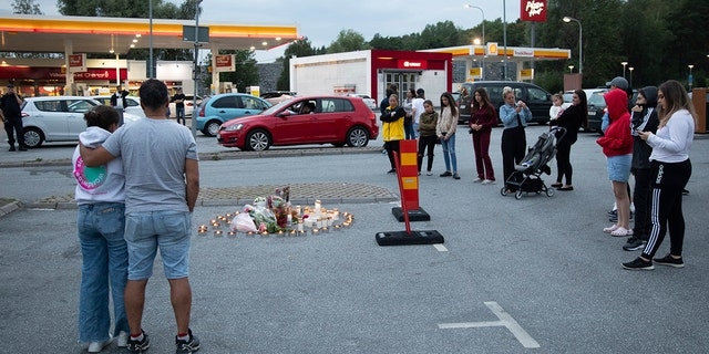 Flowers and candles are placed Sunday Aug. 2, 2020 near where a twelve-year-old girl was shot and killed near a petrol station in Botkyrka, south of Stockholm, Sweden. (Ali Lorestani//TT via AP)