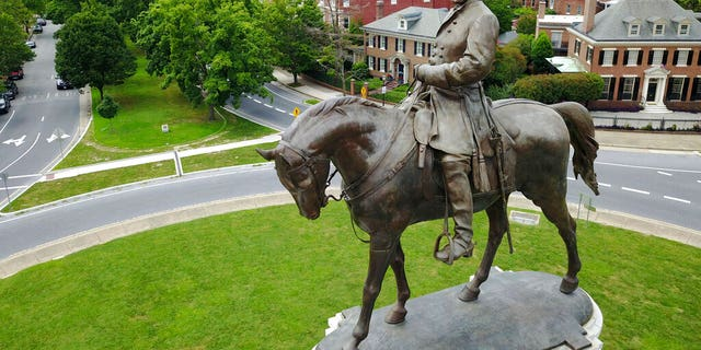 A statue of Confederate General Robert E. Lee standing in the middle of a traffic circle on Monument Avenue in Richmond, Va.