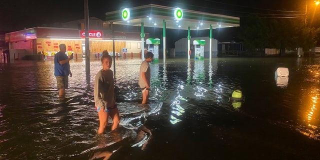 People are walking on the flooded Sea Mountain Highway in North Myrtle Beach, SC when Isaias approached the Carolinas on Monday evening August 3, 2020.  (Jason Lee / The Sun News via AP)