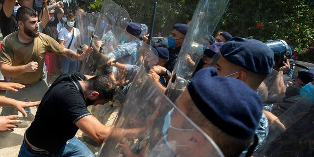 Riot police scuffle with anti-government protesters outside the Ministry of Energy and Water in Beirut, Lebanon, Tuesday, Aug. 4, 2020. (AP Photo/Hassan Ammar)