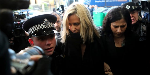 In this Dec. 23, 2019 photo, 'Love Island' TV presenter Caroline Flack (center) as she arrives at Highbury Magistrates' Court in London. A British coroner has ruled Thursday Aug. 6, 2020, that reality TV host Caroline Flack killed herself while facing an assault trial she feared would end her career and bring unbearable media scrutiny. (AP Photo/Petros Karadjias, FILE)