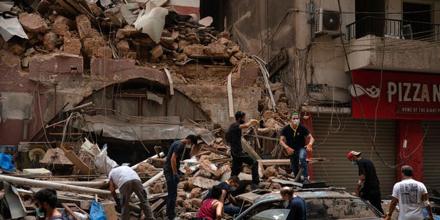 People remove debris from a house damaged by Tuesday's explosion in the seaport of Beirut, Lebanon, Friday, Aug. 7, 2020. Rescue teams were still searching the rubble of Beirut's port for bodies on Friday, nearly three days after the massive explosion sent a wave of destruction through Lebanon's capital. (AP Photo/Felipe Dana)