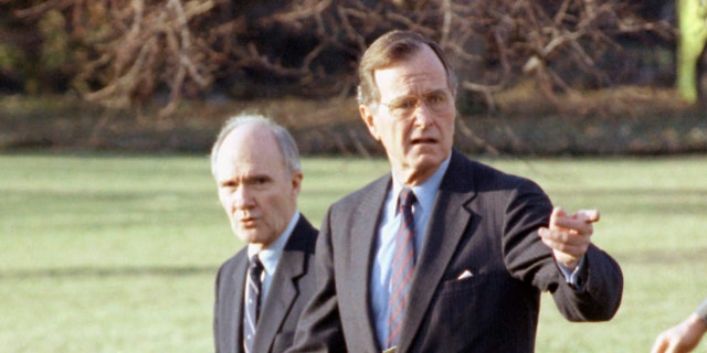 In this Feb. 6, 1990 file photo, President George H. W. Bush gestures as he and National Security Adviser Brent Scowcroft walk to the presidential helicopter on the South Lawn of the White House in Washington. (AP Photo/Barry Thumma)