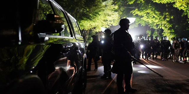 Portland police officers on Saturday, Aug. 8, 2020 in Portland, Ore. (AP Photo/Nathan Howard)