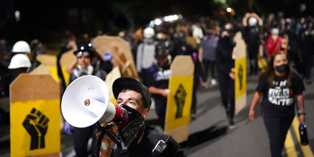 A protester leads a crowd of demonstrators toward the Multnomah County Sheriff's Office on Saturday, Aug. 7, 2020 in Portland, Ore. (AP Photo/Nathan Howard)