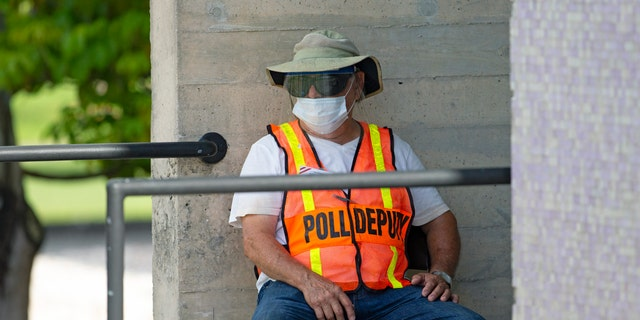 A worker waiting outside the polling place during early primary voting at the Miami Dade College North Campus in Miami on Aug. 9.