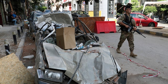 A soldier walks past damaged vehicles, Monday, Aug. 10, 2020, in Beirut, Lebanon, near the site of last week's explosion that hit the city's seaport. (AP Photo/Bilal Hussein)