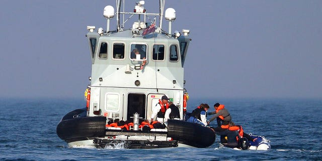 A Border Force vessel assist a group of people thought to be migrants on board from their inflatable dinghy in the Channel, Monday Aug. 10, 2020.(Gareth Fuller/PA via AP)
