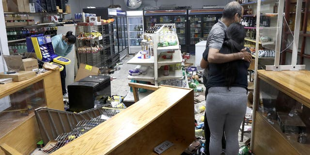 Yogi Dalal squeezes his daughter Jigisha, like his second daughter Kajal, to the left, bending his head at the family's grocery store on Monday, August 10, 2020, after the family business was ravaged in Chicago.  (AP Photo / Charles Rex Arbogast)