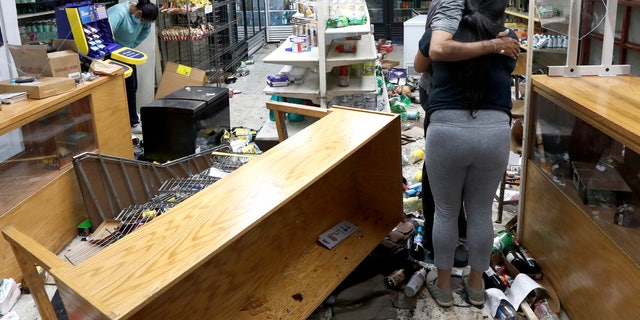 Yogi Dalal hugs his daughter Jigisha as his other daughter Kajal, left, bows her head at the family food and liquor store Monday, Aug. 10, 2020, after the family business was vandalized in Chicago. (AP Photo/Charles Rex Arbogast)