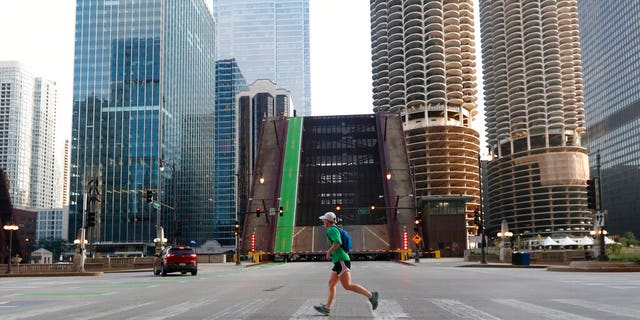 A jogger passes Monday, August 10, 2020, the elevated Dearborn Street Bridge over the Chicago River following overnight vandalism in Chicago.