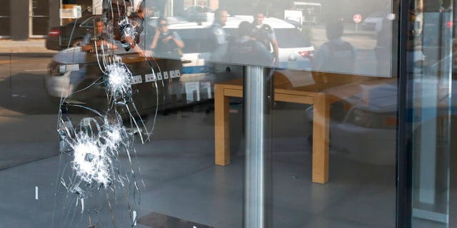 Chicago police officers are reflected in a broken window as they gather, Monday, August 10, 2020, outside an Apple Store that was vandalized overnight in Lincoln Park, Chicago.