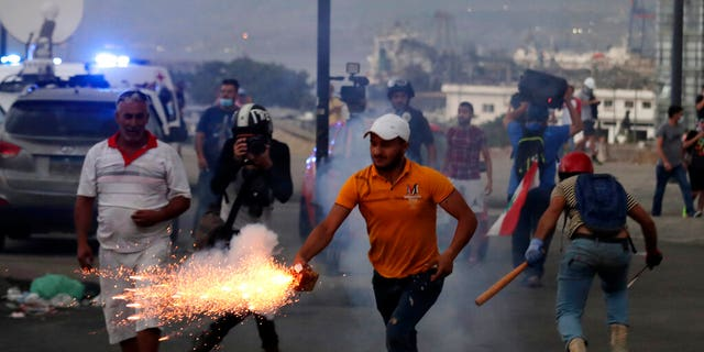 Anti-government protesters use fireworks against Lebanese riot police during a protest in the aftermath of last Tuesday's massive explosion. (AP Photo/Hassan Ammar)