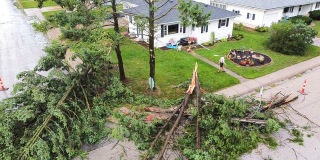 Downed trees and a utility pole in front of the home of Tim and Patricia Terres in Walcott, Iowa after high winds and heavy rain passed through the area Monday, Aug. 10, 2020, in Davenport, Iowa.