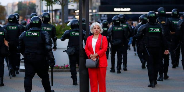 A woman stands in a street as police gather to block protesters during a mass protest following presidential elections in Minsk, Belarus, Monday, Aug. 10, 2020.