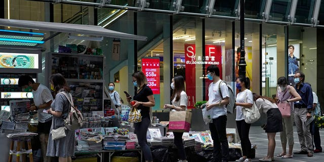 People lined up at the newsstand to buy copies of Apple Daily in a central street in Hong Kong on Tuesday, August 11, 2020, as an endorsement, a day after founder Jimmy Lai was arrested.
