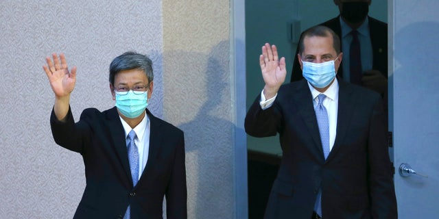 Azar and Taiwan former Vice President Chen Chien-jen wave before Azar delivers a speech at National Taiwan University College of Public Health in Taipei, Taiwan Tuesday, Aug. 11, 2020. (AP Photo/Chiang Ying-ying)