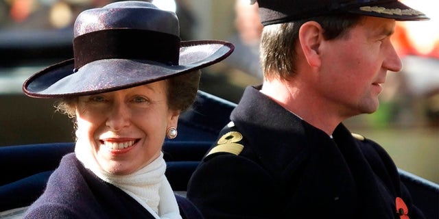 FILE - In this Nov. 6, 2001 file photo, Britain's Princess Anne with her husband Commander Tim Lawrence ride in a ceremonial carriage through Windsor town centre, where they were guests of Queen Elizabeth II at Windsor Castle to welcome King Abdullah and Queen Rania of Jordan on their state visit to England. (AP Photo/Dave Caulkin/File)