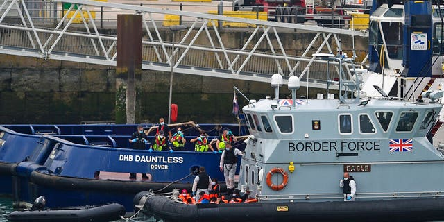 A group of people thought to be migrants are brought into Dover, England, Wednesday, Aug. 12, 2020, by Border Force officers. (Kirsty O'Connor/PA via AP)