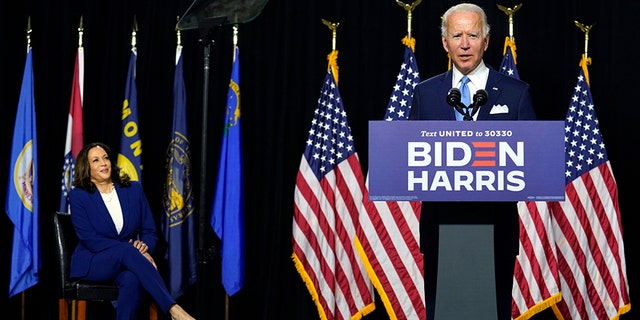 Democratic presidential candidate former Vice President Joe Biden speaks as his running mate Sen. Kamala Harris, D-Calif., listens during a news conference at Alexis Dupont High School in Wilmington, Del., Wednesday, Aug. 12, 2020. (AP Photo/Carolyn Kaster)