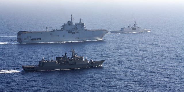 In this photo provided by the Greek National Defense, a French helicopter carrier Tonnerre, the rear left is accompanied by Greek and French military ships during a naval exercise in the Eastern Mediterranean, Thursday, August 13, 2020.