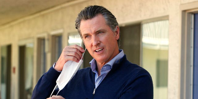 FILE: Gov. Gavin Newsom removes his face mask before giving an update on the state's initiative to provide housing for homeless Californians amid the coronavirus pandemic, during a visit to Pittsburg, Calif. in June.