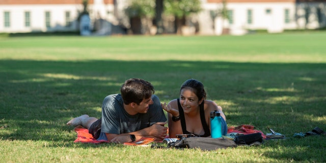 Students sit in partial shade on the quad at the University of Alabama on Saturday, Aug. 15, 2020, in Tuscaloosa, Ala. More than 20,000 students returned to campus Saturday for the first time since spring break. (AP Photo/Vasha Hunt)
