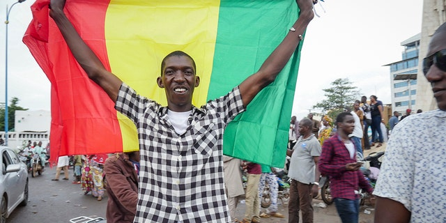 A man holds a national flag as he celebrates with others in the streets in the capital Bamako, Mali Tuesday, Aug. 18, 2020. Mutinous soldiers detained Mali's president and prime minister Tuesday after surrounding a residence and firing into the air in an apparent coup attempt after several months of demonstrations calling for President Ibrahim Boubacar Keita's ouster. (AP Photo)