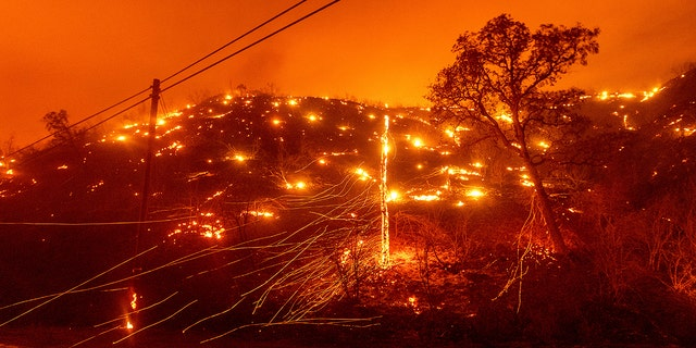Seen in a long exposure photograph, embers burn along a hillside as the LNU Lightning Complex fires tear through unincorporated Napa County, Calif., on Aug. 18.