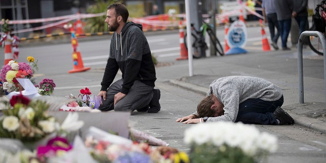 In this March 19, 2019, file photo, mourners pray near the Linwood mosque in Christchurch, New Zealand. More than 60 survivors and family members will confront the New Zealand mosque gunman during the four-day sentencing starting Monday, Aug. 24, 2020.(AP Photo/Vincent Thian, File)