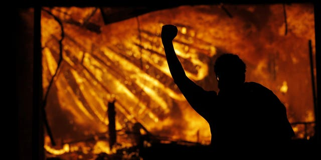 In this May 28, 2020 file photo, a protester gestures in front of the burning 3rd Precinct building of the Minneapolis Police Department in Minneapolis. (AP Photo/Julio Cortez File)