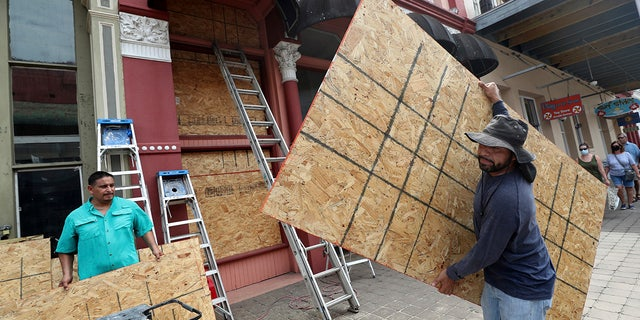 Métis - Cesar Reyes, right, carries a sheet of plywood to cut to size as he and Robert Aparicio, left, install window coverings at Strand Brass and Christmas on the Strand, 2115 Strand St., in Galveston on Monday, Aug. 24, 2020. ( Jennifer Reynolds/The Galveston County Daily News via AP)
