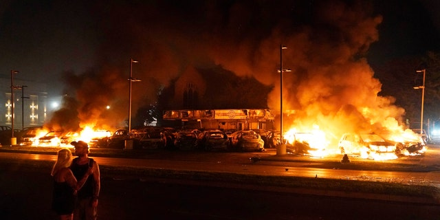 Bystanders look on as cars burn after protesters set fire to a used auto lot late Monday, Aug. 24, 2020, in Kenosha, Wis. (AP Photo/David Goldman)