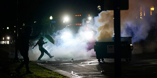 A protester kicking a smoke canister Tuesday in Kenosha, Wis. Anger over the Sunday shooting of Jacob Blake, a Black man, by police spilled into the streets for a third night. (AP Photo/Morry Gash)