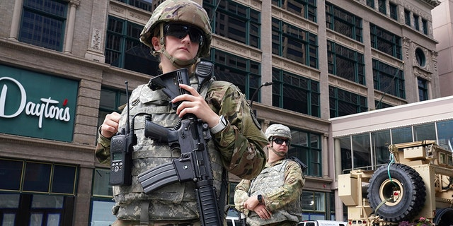 Members of the Minnesota National Guard stand at the intersection of South 7th Street and Nicollet Mall in Minneapolis, 星期四, 八月. 27, 2020, as community members and business owners clean up damage from looters.  (Anthony Souffle/Star Tribune via AP)