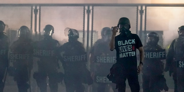 A protester holds up a phone as he stands in front of authorities in Kenosha, Wis. (AP Photo/Morry Gash, File)