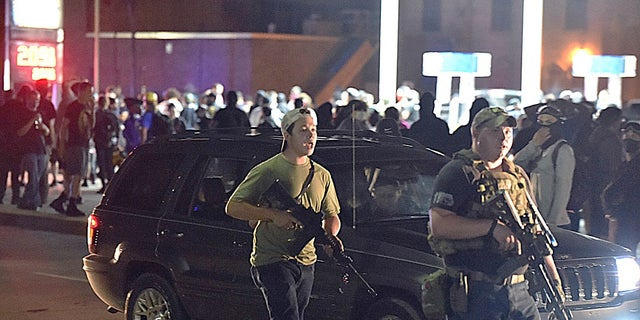 Kyle Rittenhouse, left, with backwards cap, walks along Sheridan Road in Kenosha, Wis., on Tuesday with another armed civilian. (Adam Rogan/The Journal Times via AP)