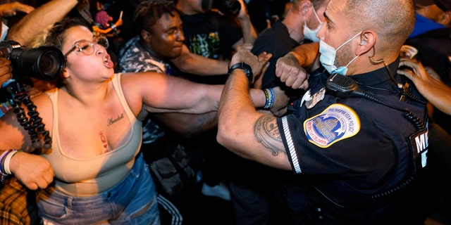 Metropolitan Police are confronted by protestors as police carry away a handcuffed protestor along a section of 16th Street, Northwest, renamed Black Lives Matter Plaza, Thursday night , Aug. 27, 2020, in Washington, after President Donald Trump had finished delivering his acceptance speech from the White House South Lawn. (AP Photo/Julio Cortez)