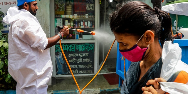 A civic worker sprays sanitizers in front of a shop as a woman wearing face mask walks past in Kolkata, India, Sunday, Aug. 30, 2020. India has the third-highest coronavirus caseload after the United States and Brazil, and the fourth-highest death toll in the world. (AP Photo/Bikas Das)