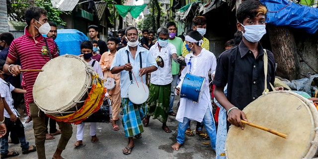 Muslims wearing face masks beat drums during a Muharram procession in Kolkata, India, Sunday, Aug. 30, 2020. India has the third-highest coronavirus caseload after the United States and Brazil, and the fourth-highest death toll in the world. (AP Photo/Bikas Das)
