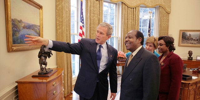In this Thursday, Feb. 17, 2005, file photo provided by the White House, President Bush, left, and first lady Laura Bush, second right, meet with Paul Rusesabagina, center-right, and his wife, Tatiana, right, in the Oval Office. (Eric Draper/The White House via AP )