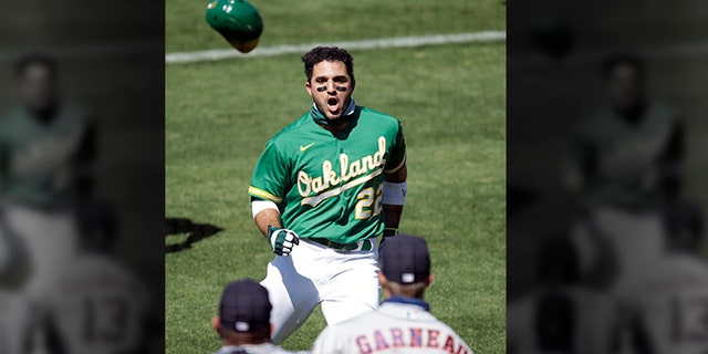Oakland Athletics' Ramon Laureano (22) charges the Houston Astros dugout after being hit by a pitch thrown by Astros' Humberto Castellanos in the seventh inning of a baseball game Sunday, Aug. 9, 2020, in Oakland, Calif.