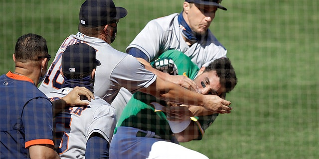 Oakland Athletics' Ramon Laureano is restrained by Houston Astro's Dustin Garneau after Laureano charged the dugout after being hit by a pitch thrown by Humberto Castellanos in the seventh inning of a baseball game Sunday, Aug. 9, 2020, in Oakland, Calif.