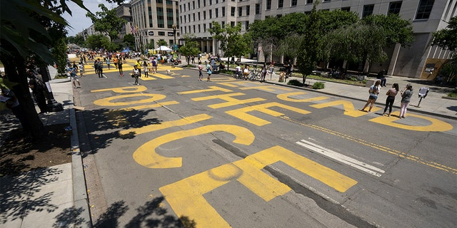"""""""Defund the Police"""" is painted on the street in Black Lives Matter Plaza near the White House in Washington, D.C., on Sunday, June 14, 2020. (Stefani Reynolds/Bloomberg via Getty Images)"""