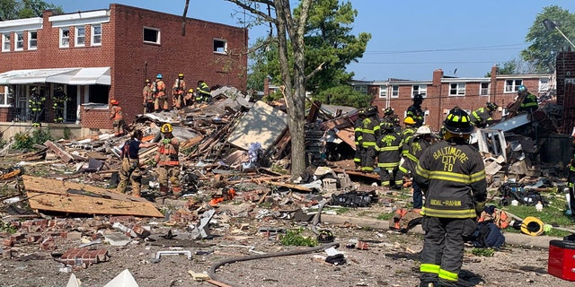 Baltimore firefighters searched for victims of a gas explosion Monday that leveled three row houses and killed a woman.