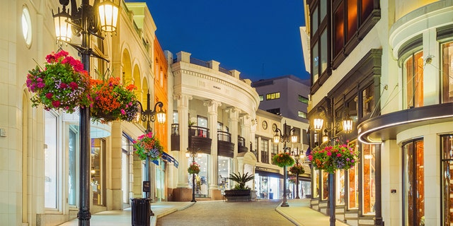 Photo of Rodeo Drive with illuminated stores in Beverly Hills, Calif., at twilight blue hour.