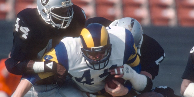 Mike Guman #44 of the Los Angeles Rams gets tackled by Howie Long #75 and Burgess Owens #44 of the Los Angeles Raiders during an NFL football game, Dec. 18, 1982. (Focus on Sport/Getty Images)