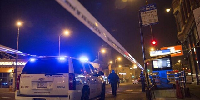 Chicago police officers investigate a crime scene of a gunshot victim. The police department reported 25 people shot and four killed during a day of gun violence across the city on Monday. ( REUTERS/Jim Young)