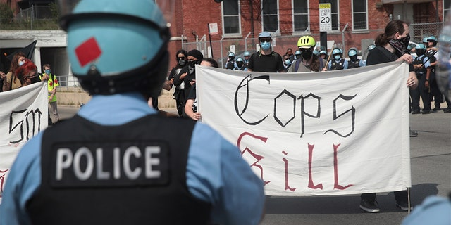 Police stand guard as pro and anti-police demonstrators gather outside of the Homan Square police station on August 15, 2020 in Chicago, Illinois. (Photo by Scott Olson/Getty Images)