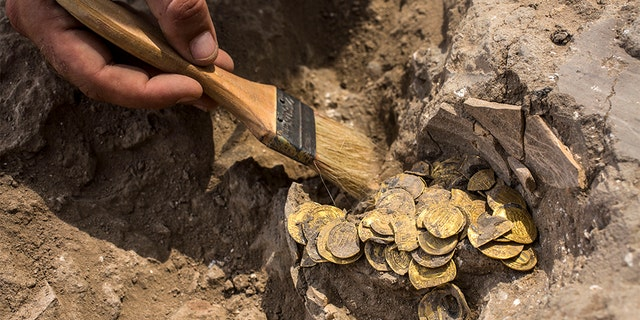 """Israeli archaeologist Shahar Krispin cleans gold coins that was discovered at an archeological site in central Israel, Tuesday, Aug 18, 2020. Israeli archaeologists have announced the discovery of a trove of early Islamic gold coins during recent salvage excavations near the central city of Yavn Tel Aviv. The collection of 425 complete gold coins, most dating to the Abbasid period around 1,100 years ago, is a """"extremely rare"""" find. (AP Photo/Sipa Press, Heidi Levine, Pool)"""